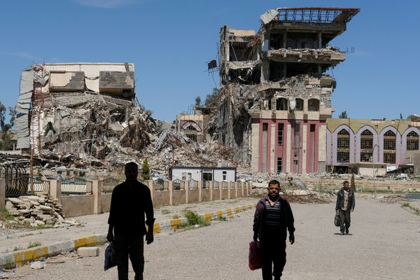 People walk in front of the remains of the University of Mosul, which was burned and destroyed during a battle with Islamic S