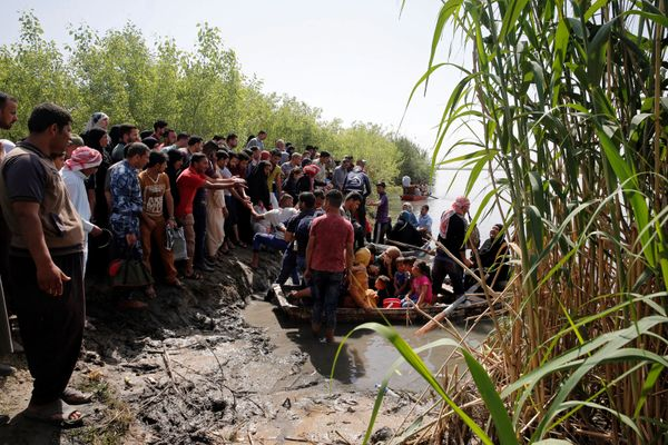 Displaced Iraqis from Mosul wait to cross the Tigris by boat after the bridge had been temporarily closed, at the village of