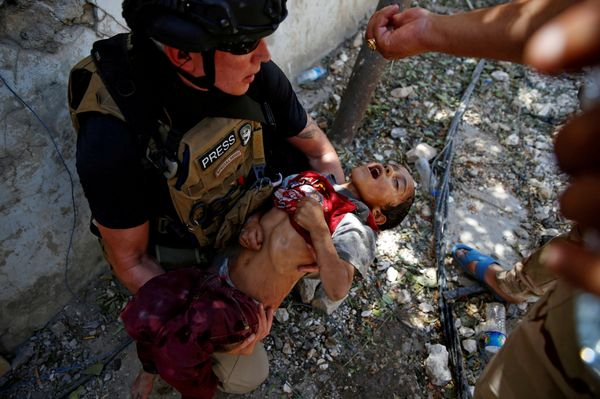 An Iraqi soldier from the 9th Armoured Division gives drops of water to a dehydrated child rescued earlier by soldiers at the