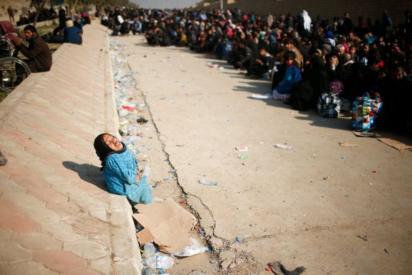 A displaced Iraqi woman reacts as she waits in a street for a truck to carry her to a safe place, as Iraqi forces battle with