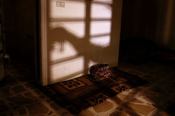 The shadow of a member of the Iraqi Army's 9th Armoured Division is seen as he opens a steel gate to a room used as a cell fo