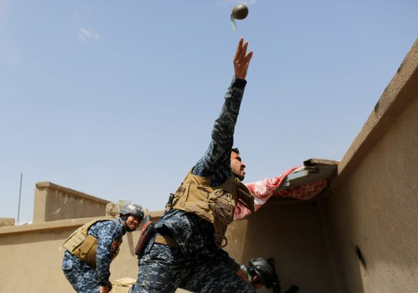 A member of the Iraqi Federal Police throws a hand grenade during clashes with the Islamic State fighters on April 29, 2017.&