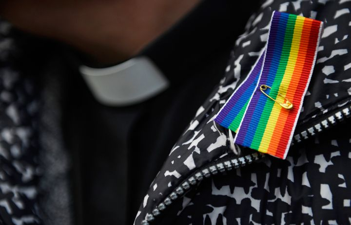 A priest wears a rainbow ribbon during a vigil against Anglican Homophobia, outside the General Synod of the Church of Englan