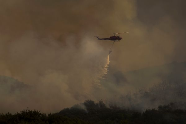 A firefighting helicopter drops water on the Whittier Fire.