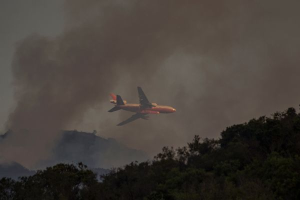 A DC-10 firefighting jet flies low through the smoke of the Whittier Fire on July 9, 2017 near Santa Barbara, California.&nbs