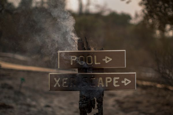 A sign smolders near structures at Rancho Alegre Boy Scouts of America outdoor school that were destroyed by the Whittier Fir
