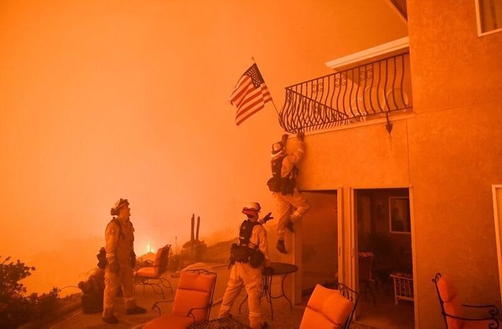 Firefighters save a US flag as impending flames from the Wall fire close in on a luxury home in Oroville, California on July