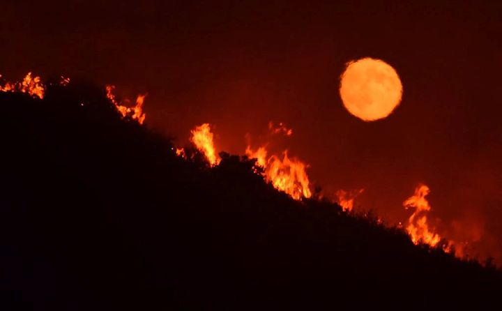 The full moon rises over flames of the Alamo fire in Santa Maria, California, on July 7.