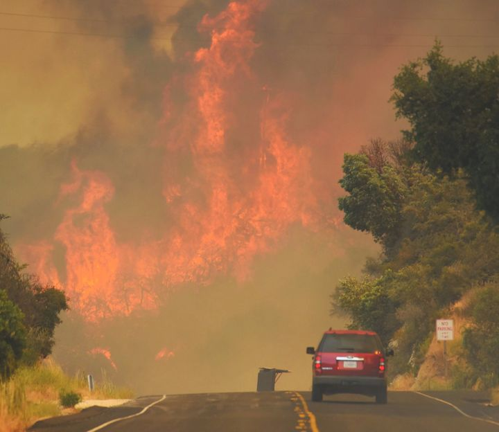 A Santa Barbara city fire vehicle drives towards flames from the Whittier Fire on July 8.