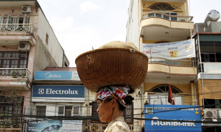 A woman carries a basket of bread for sale on her head on a street in Hanoi.