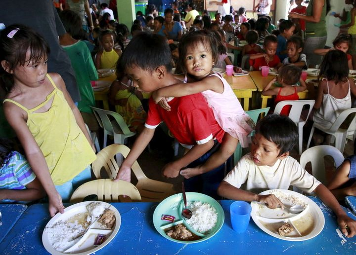 Children eat free meals distributed by group World Mission Community Care in a slum in Manila.