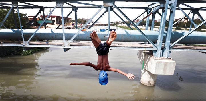 A boy jumps from a water pipe into a canal as temperatures soar in New Delhi. Access to clean and regular water remains a ch