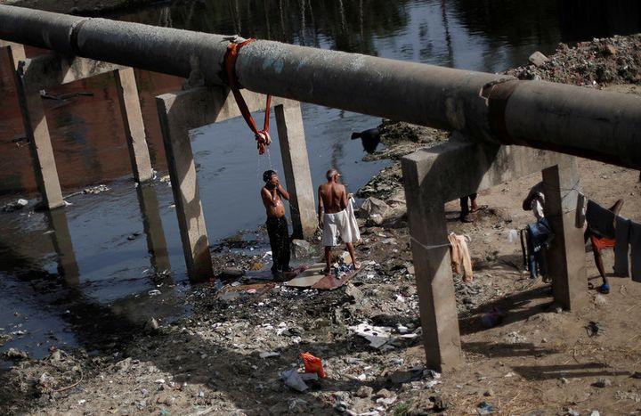 A man bathes under a broken water pipeline in New Delhi, India June 5, 2017.
