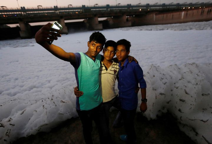 Boys pose for a selfie in front of the foam covering the polluted Yamuna river in New Delhi, November 2016.