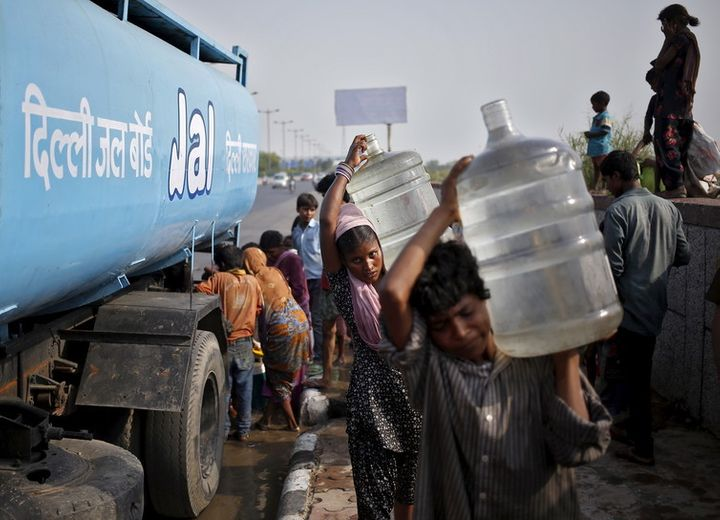 Slum dwellers carry filled water container from a tanker provided by the state-run Delhi Jal Board.