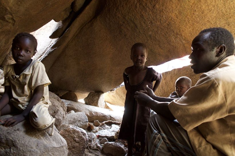 A family shelters in a cave in the Nuba Mountains, to avoid bombings by the Sudan government.