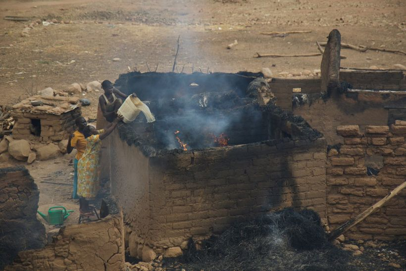 Women in the Nuba Mountains work to put out a fire, after a home was bombed by Sudan war planes.