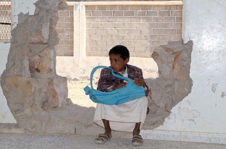 Garoto sentado em um buraco em um muro de uma escola atingida no conflito em curso na província de Saada....