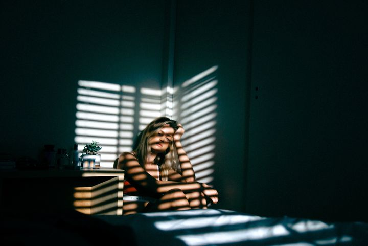 <p>Young woman sitting in the shadows looking sad</p>