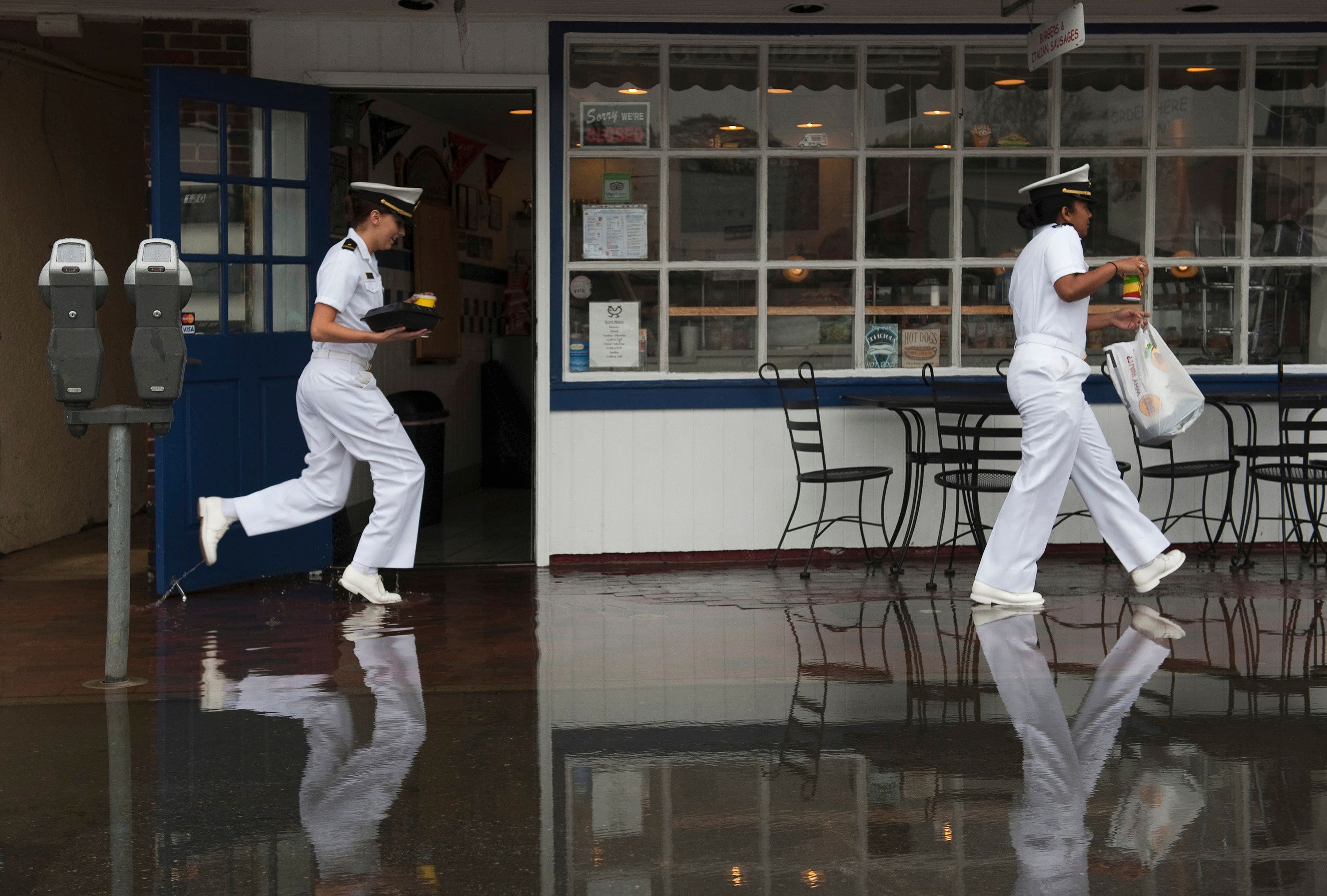 "U.S. Naval Academy Midshipmen who declined to give their names, tiptoe through the water in front of ""Pip's Dock Street Dogs"" after the Chesapeake Bay overflowed its banks at City Dock in Annapolis, Maryland May 16, 2014. Picture taken May 16, 2014. To match Special Report SEALEVEL-FLOODING/CHESAPEAKE REUTERS/Mary F. Calvert (UNITED STATES - Tags: ENVIRONMENT SOCIETY MILITARY MARITIME)"