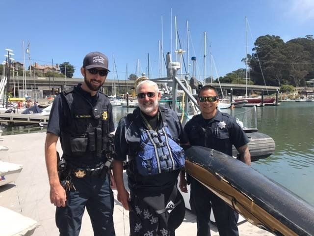 Seasoned California kayaker Steve Lawson smiles with officers after being attacked by a great white shark