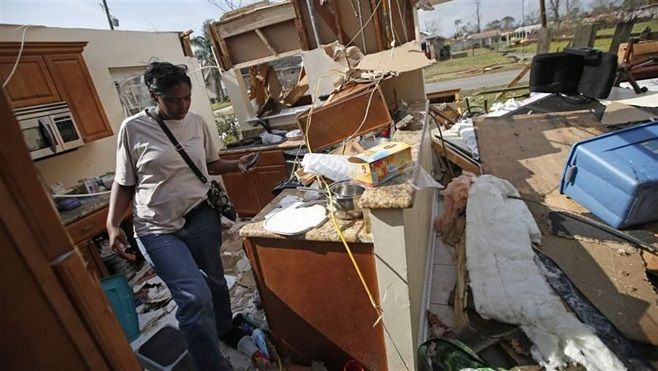 Carla Wilson walks through a house in the New Orleans East neighborhood following a February tornado that destroyed homes and