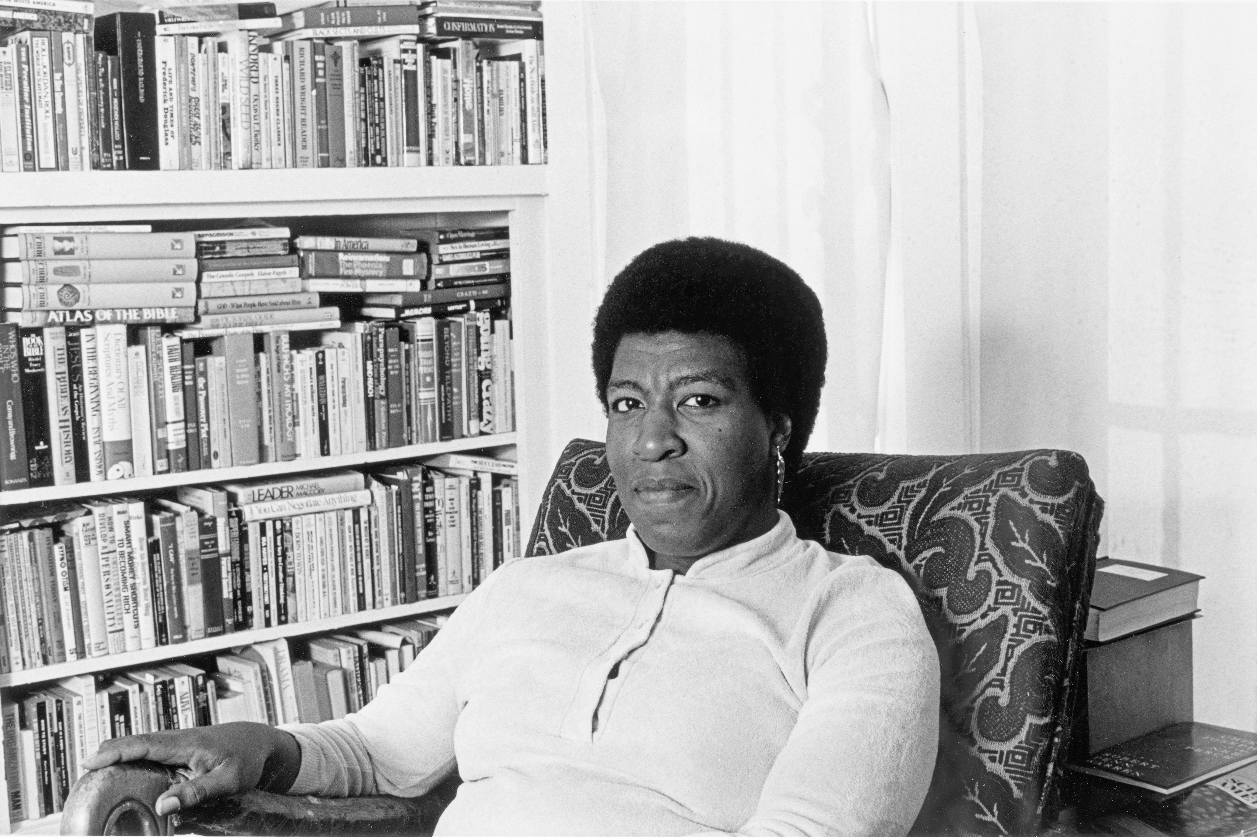 Octavia E Butler seated by her bookcase, 1986.