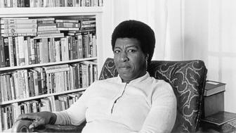 Octavia E Butler seated by her bookcase 1986