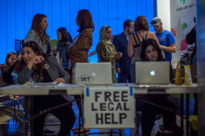 Attorneys offer free legal help to arriving international travelers on the first day of the the partial reinstatement of the