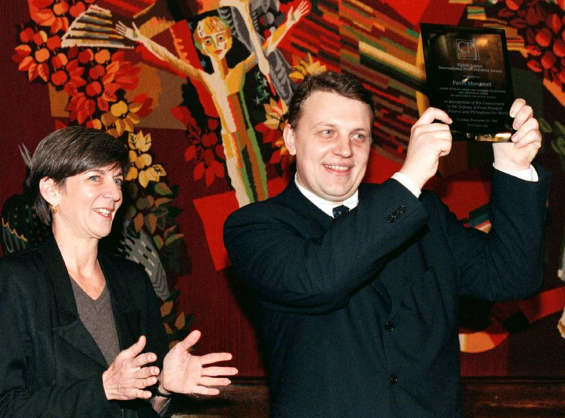 Pavel Sheremet, pictured with CPJ's then-executive director Ann Cooper, lifts his International Press Freedom Award during a