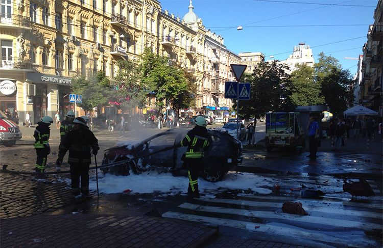 In this photograph taken by Olena Prytula before she realized her partner was in the explosion, firefighters douse the vehicl