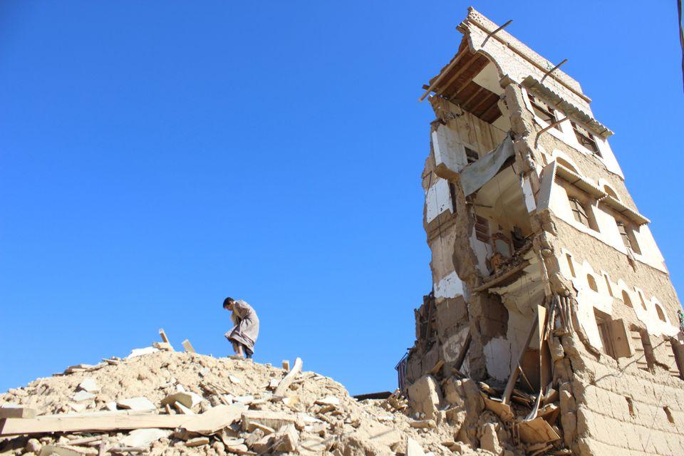 Um garoto caminha sobre os escombros de uma casa destruída por um ataque aéreo recente liderado pelos...