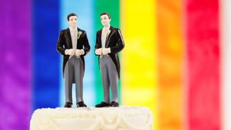 Subject: Same sex marriage wedding cake with two male groom figurine cake toppers and rainbow flag in background.