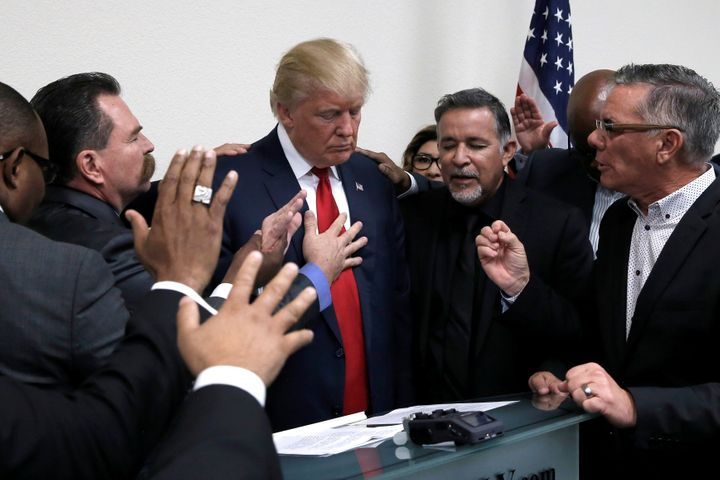 Republican presidential nominee Donald Trump prays with pastors during a campaign visit to the International Church of Las Ve