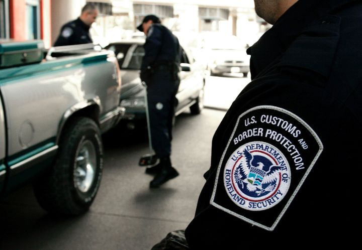 U.S. Customs and Border Protection agents inspect a vehicle coming into the U.S.