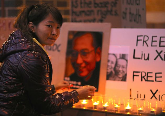 A member of the Tibetan community in Australia attends a candlelight vigil for Liu Xiaobo outside the...