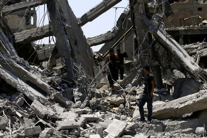 Iraqi security forces walk along destroyed buildings from clashes in the Old City of Mosul on July 10.
