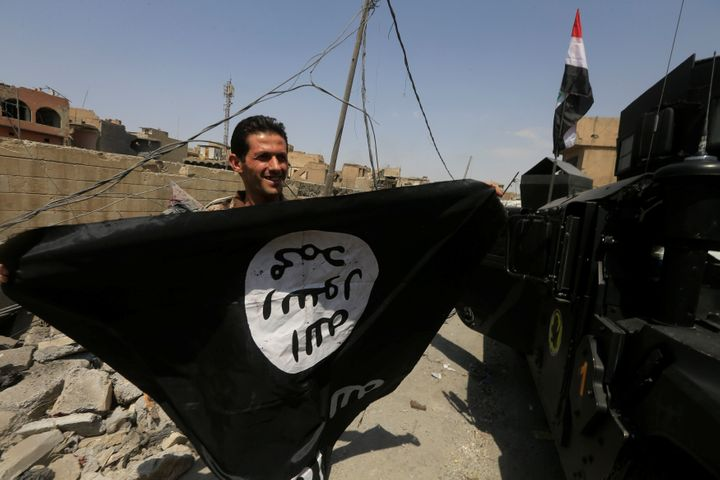 A member of Iraqi Counter Terrorism Service holds an Islamic State flagas he celebrates in the Old City of Mosul on Jul
