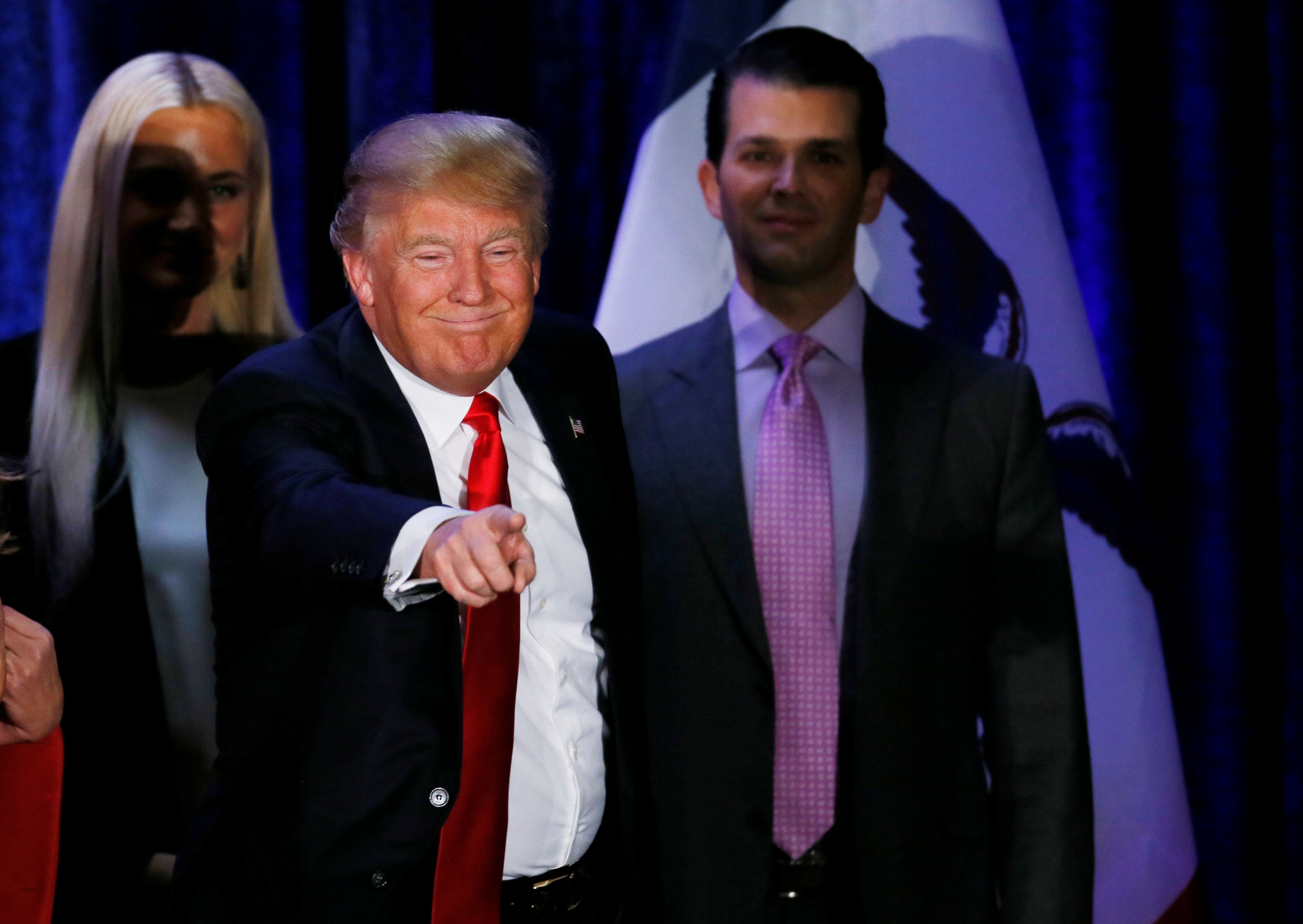 Republican U.S. presidential candidate Donald Trump gestures to the crowd as he leaves the stage flanked by his son Donald Trump Jr. (R) and Trump Jr's wife Vanessa (L) on the night of the Iowa Caucus in Des Moines, Iowa U.S. February 1, 2016.   REUTERS/Jim Bourg