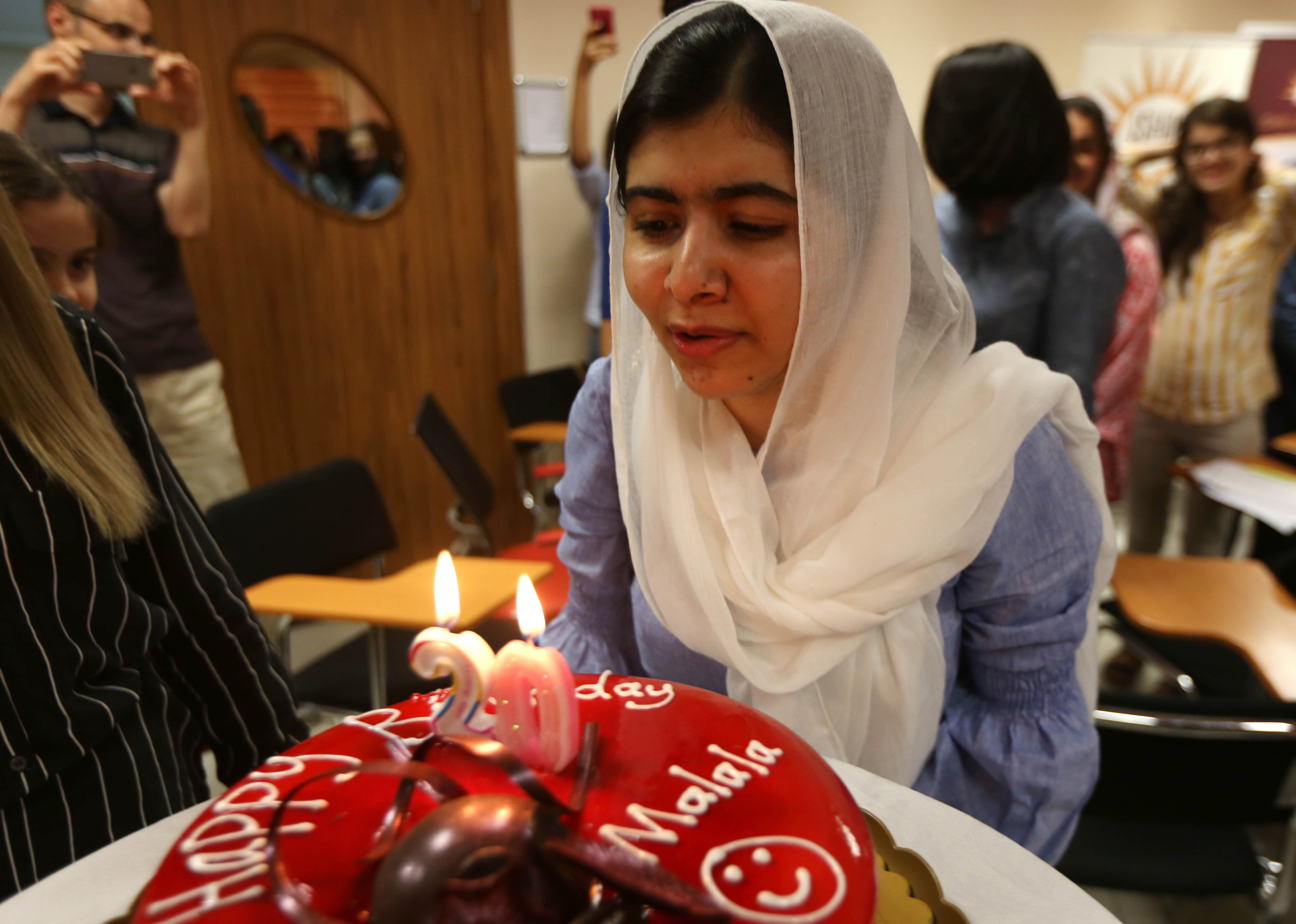 Pakistani Nobel Peace Laureate Malala Yousafzai (C) blows out candles on a cake on the eve of her birthday as she meets with students of the University in Arbil, the capital of the autonomous Kurdish region of northern Iraq, on July 11, 2017. / AFP PHOTO / SAFIN HAMED        (Photo credit should read SAFIN HAMED/AFP/Getty Images)