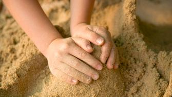 A child is forming a cone shape out of sand.