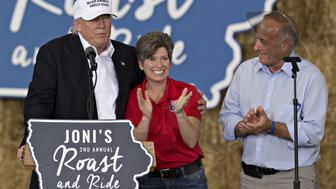 Donald Trump, 2016 Republican presidential nominee, left, stands on stage with Senator Joni Ernst, a Republican from Iowa, center, and Representative Steven 'Steve' King, a Republican from Iowa, at the conclusion of the 2nd annual Roast and Ride hosted by Ernst in Des Moines, Iowa, U.S., on Saturday, Aug. 27, 2016. Ernst, who in 2014 won the Senate seat vacated by Democrat Tom Harkin when he retired, has turned her Roast and Ride into the conservative answer to the Harkin's legendary Steak Fry fundraiser, which auditioned dozens of presidential candidates over its 37-year history. Photographer: Daniel Acker/Bloomberg via Getty Images