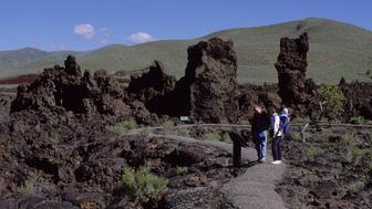 UNITED STATES - 1991/06/30: Visitors (Model Release19870820-1 + 20020923-10) in the lava field at Craters of the Moon National Monument in Idaho, USA, which formed during eight major eruptive periods between 15,000 and 2000 years ago. Lava erupted from the Great Rift, a series of deep cracks that start near the visitor center and stretch 52 miles (84 km) to the southeast and formed an area of 618 square miles (1600 square km). (Photo by Wolfgang Kaehler/LightRocket via Getty Images)