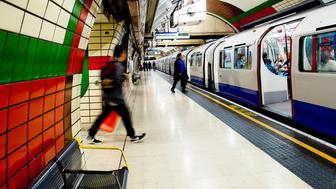 London, United Kingdom - October 8, 2014: View of the London Underground subway Piccadilly Line with train at station platform with people visible.  The Underground, also known as the Tube, is a rapid transit system serving the greater London area.