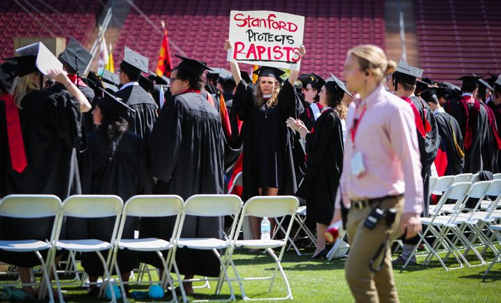 A woman carries a sign in solidarity for a Stanford rape victim during graduation at Stanford University on June 12, 2016. St
