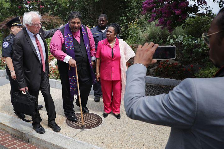 Sen. Bernie Sanders (I-VT) (L) and Rep. Sheila Jackson Lee (D-TX) walk with NAACP North Carolina President Rev. Dr. William B