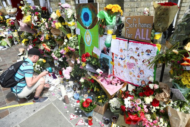 <strong>A man leaves a tribute for the victims of the Grenfell Tower fire.</strong>