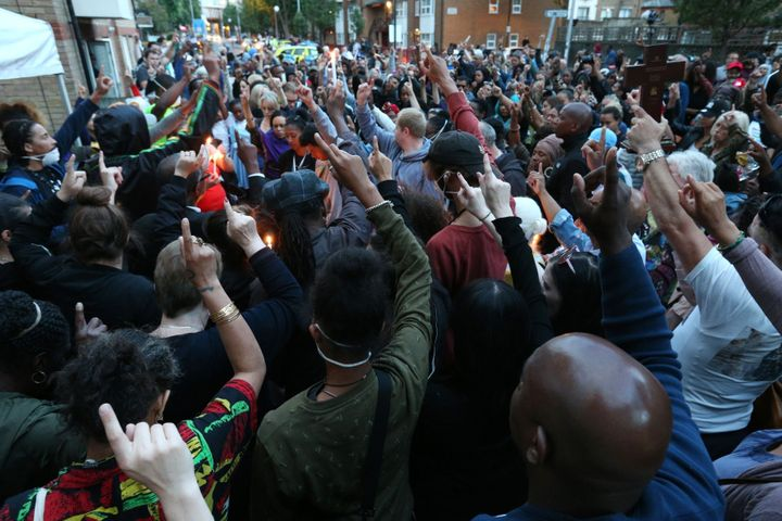<strong>People attend a vigil to mark four weeks since the Grenfell Tower fire, at the memorial wall on Bramley Road, London.</strong>