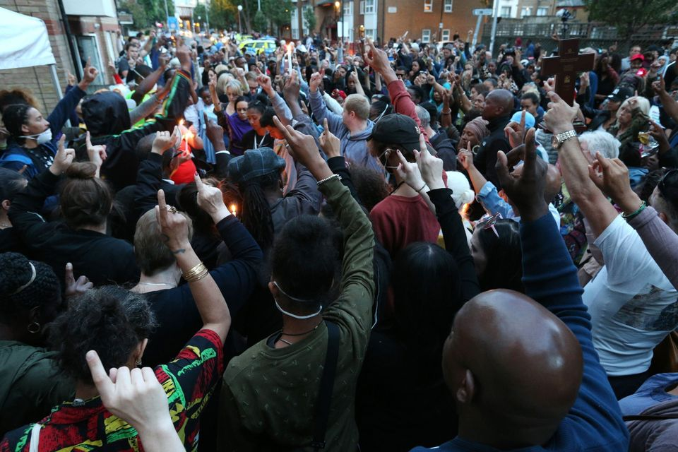 People attend a vigil to mark four weeks since the Grenfell Tower fire, at the memorial wall on Bramley...
