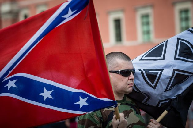 A far-right activist in Warsaw, Poland, holds a Confederate flag and a White Pride flag while taking...